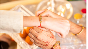 Sister tying the Rakhi on her brother's wrist